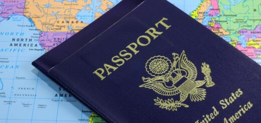 close-up photo of two American passport lying on top of a world map