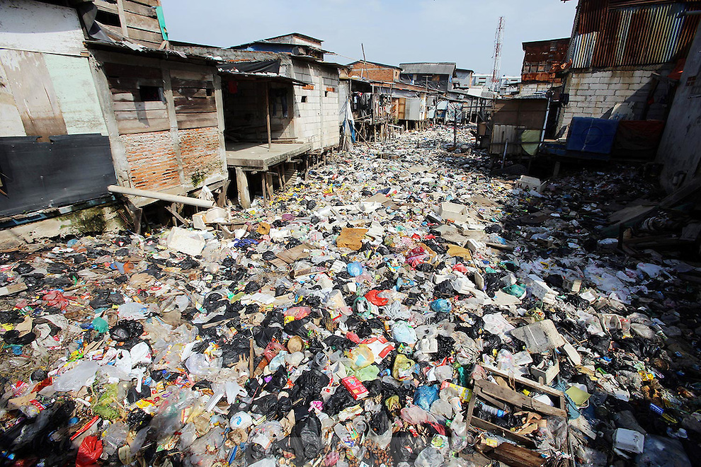 a slum area with canal full of trashes