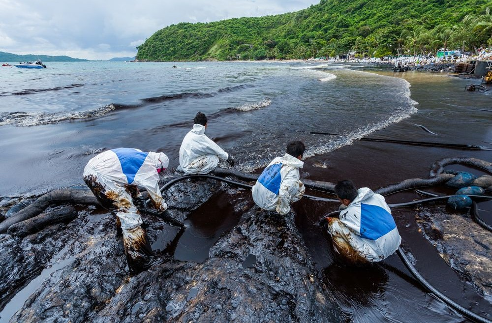 four men in safety suits working on a shore to clean up oil spill