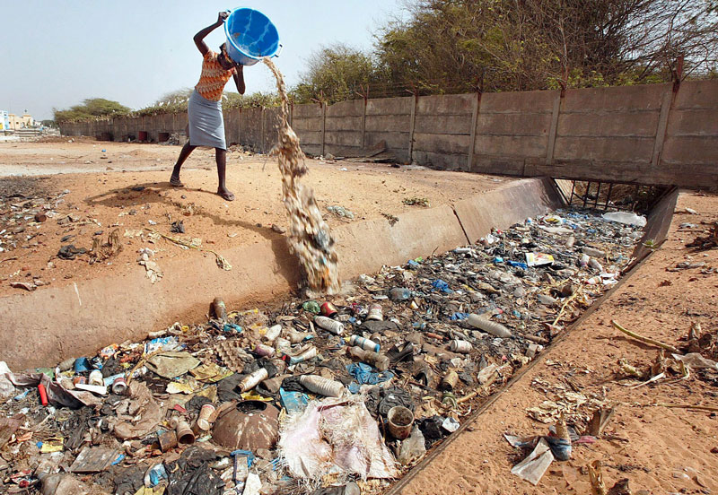 a woman dumping a pail of garbage into a water canal full of trashes