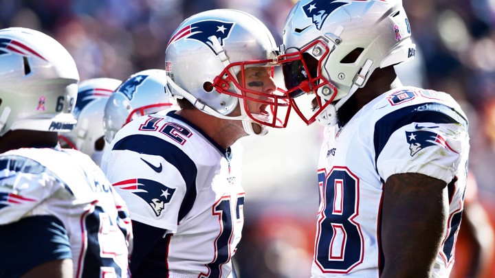 two football players closely talking to each other