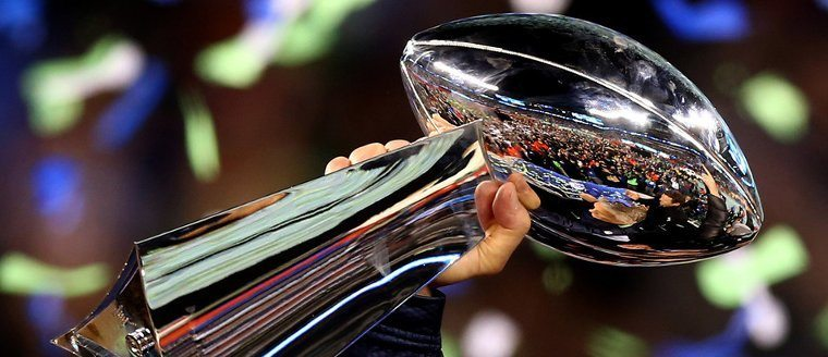 close-up photo of super bowl trophy held in hand