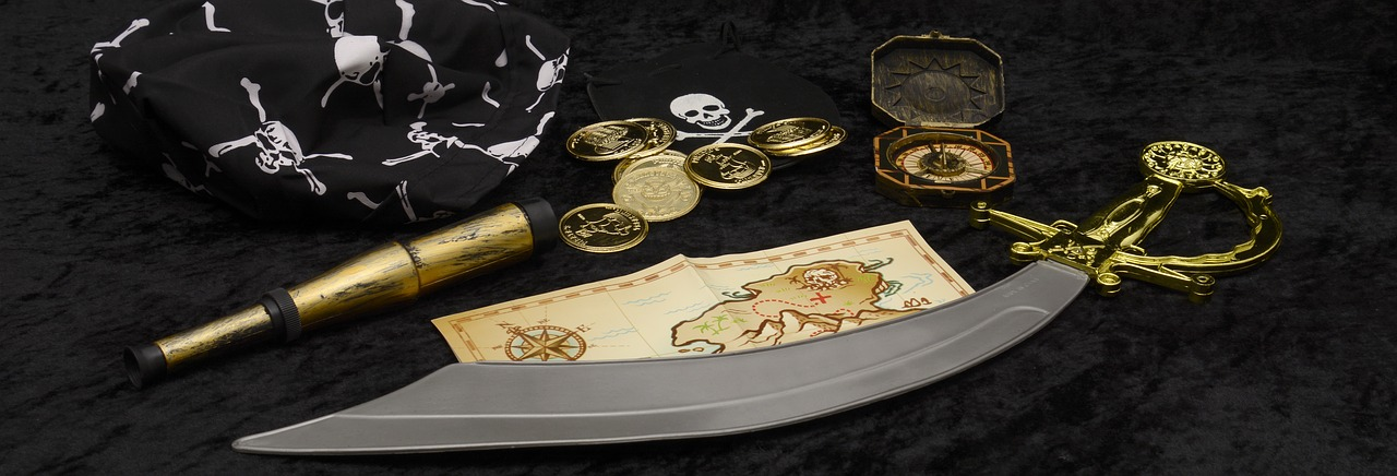 treasure map, sword, compass and other items that represents the history of pirates