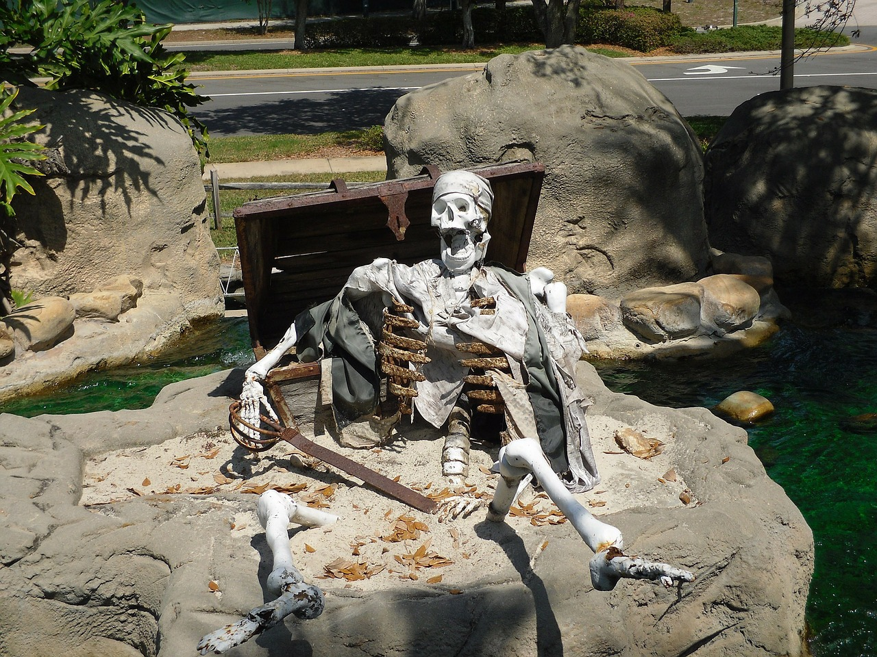a sculpture depicting the skeletal bones of a pirate with sword and treasure chest