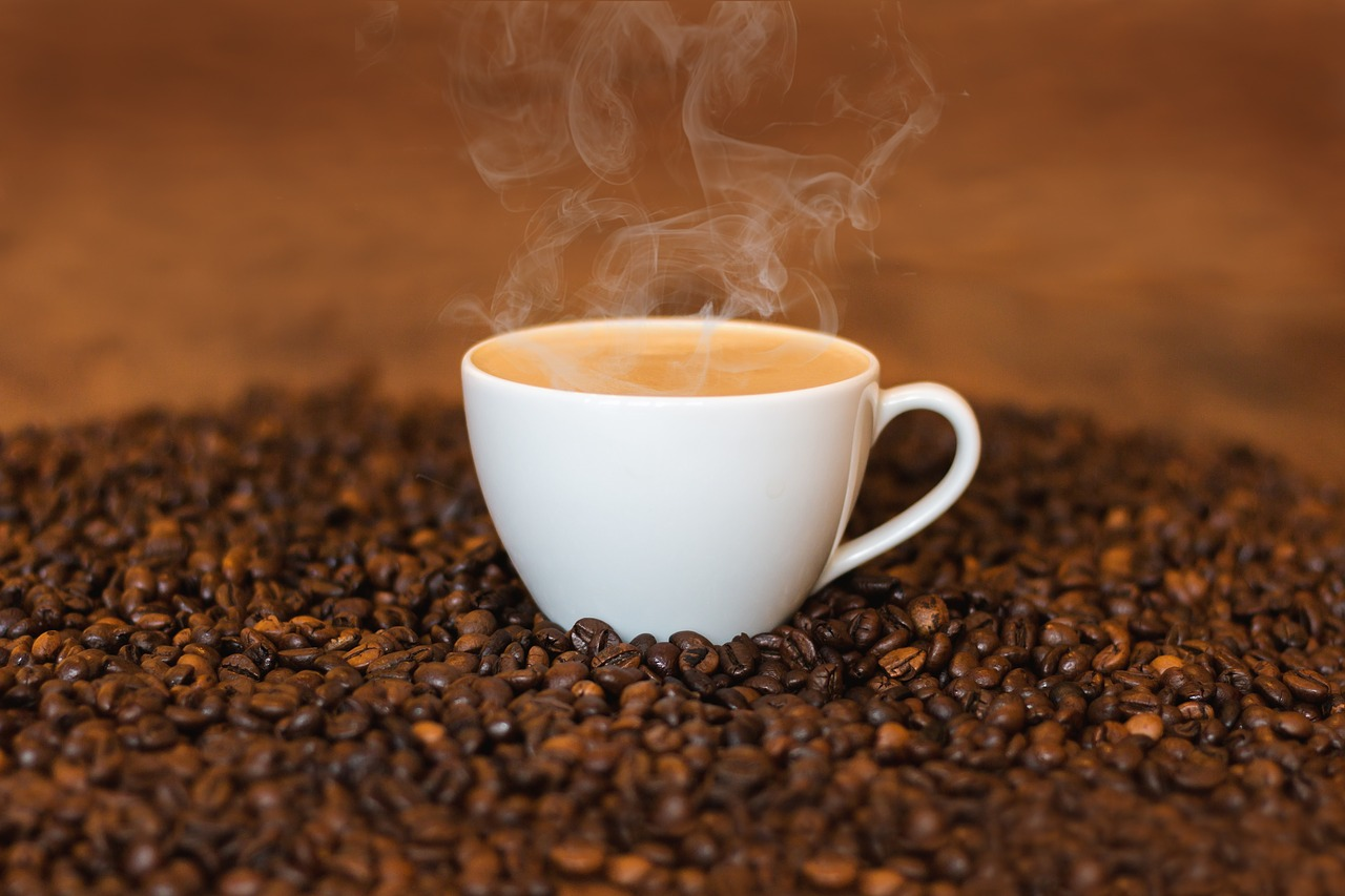 A cup of coffee on top of coffee beans